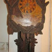 Schwarzwald-Uhr um 1910, Lindenholz gebeizt und geschnitzt mit Tannenzapfen- und Zweigen, in der Front Dorf in Berglandschaft eingebettet, Pendel aus Holz, 2 Gusseisen Zapfengewichte, B: 47cm, T:17cm, H:110cm - Preis: 350,- €
