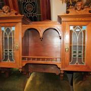 Ausgefallener Wandschrank Eiche um 1900 mit Bleiglastürfüllungen,mittig offenes Fach mit Säulchengallerie.Als Bekrönung zwei Engelsköpfe.95 cm breit,26 cm tief,78 cm hoch.  650€